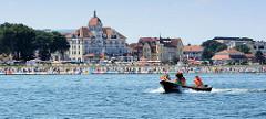 Blick von der Ostsee auf die Strandpromenade in Kühlungsborn; Hotels und Häuser mit Ferienwohnungen stehen dicht am Strand, auf dem die Strandkörbe eng beieinander stehen.