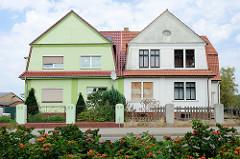 Doppelvilla in der Bahnhofstraße von Bützow, das linke Wohnhaus ist frisch restauriert und wird bewohnt - die rechte Seite ist leerstehend mit teilweise vernagelte Fenstern und einem verfallenen Zaun.