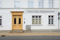 Renoviertes Gründerzeitgebäude in der Rühnerstraße von Bützow; reich verzierte Gründerzeit Holztür mit schmiedeeisernen Fenstergitter - alte Fassadenaufschrift eines Schuhmachermeisters.