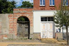Alt + Neu; verfallene Holztür / Doppeltür in einer Ziegelmauer, daneben eine restaurierte Tür mit farblich abgesetzten Leisten - Architektur in Gartz/Oder.