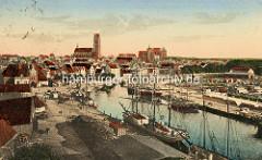 Historische, colorierte Ansicht der alten Hansestadt Wismar - Panorama vom Hafen und der Stadt. Segelschiffe liegen am Kai, der als Lagerplatz genutzt wird.