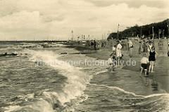 Historisches Foto vom Ostseestrand in Brunshaupten / Kühlungsborn; Kinder spielen in den Wellen der Ostsee - Strandkörbe sind aufgestellt die Touristen stehen  in Straßenanzug oder Badekleidung in Sand.