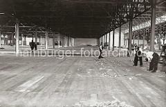 Der Verteilungsschuppen 58 als Erweiterungsbau des Schuppen 57 ist fertig gestellt; Zimmerleute arbeiten am Holzboden des Lagerschuppens, während ein anderer Arbeiter mit einem Reisigbesen den Boden reinigt.