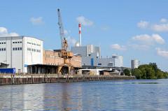 Hafenanlage mit Kran und Lagerhäusern an der Hohensaaten-Friedrichsthaler Wasserstraße, dahinter das  Ersatzbrennstoffkraftwerk.