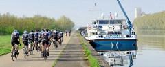 Binnenschiff am Kai des Albert Kanals in Belgien - der Hebekran für das Kfz ist ausgefahrten und das Fahrzeug an Land gebracht. Eine Gruppe Rennradfahrer fahren entlang des Kanals Richtung Lüttich.