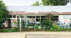 Möbel-Paradies, leerstehender Möbeldiscounter in der Philipp Müller Straße von Wismar; der Eingangsbereich ist mit jungen Bäumen und Wildkraut bewachsen, die Fensterscheiben mit Plakaten beklebt.
