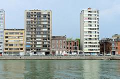 Wohnhäuser am Ufer der Maas in Lüttich / Liège; zweistöckige Wohnhäuser stehen zwischen Hochhäusern.