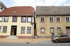 Neu und alt - Architektur der Gegensätze, Wohngebäude in Bützow;  bei dem einen ehemaligen Wohnhaus bröckelt der Fassadenputz und Fachwerk kommt zum Vorschein-die Fenster sind vernagelt. Auf der anderen Seite ein renoviertes Gebäude mit glattem Putz.