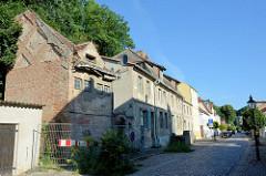 Architektur in Oderberg - Wohnhäuser in   unterschiedlichem Zustand der Bausubstanz  in der Angermünder Straße. Im Vordergrund ein verfallenes, leerstehendes Speichergebäude, dahinter ein denkmalgeschütztes Wohnhaus sowie Neubauten. Die schmale Str