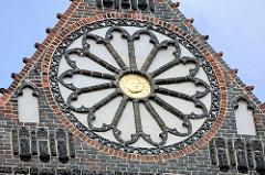 Giebel mit Terrakotta- Figuren und Rosette mit goldener Sonne im Zentrum an der Sankt Nikolaikirche in der Hansestadt Wismar.