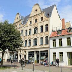 Wohn- und Geschäftshaus mit aufwändig dekorierte Jugendstilfassade in der Straße Hinter dem Chor in Wismar; Café mit Tischen auf dem Gehsteig in der Sonne.