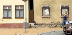 Neu und alt - Architektur der Gegensätze, Wohngebäude in Bützow;  bei dem einen ehemaligen Wohnhaus bröckelt der Fassadenputz und Fachwerk kommt zum Vorschein-die Fenster sind vernagelt. Auf der anderen Seite ein renoviertes Gebäude mit glattem Putz