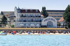 Blick auf den Ostseestrand mit Strandkörben und badenden Touristen in Kühlungsborn; dahinter Hotelgebäude wie zum Beispiel das Hansa-Haus.