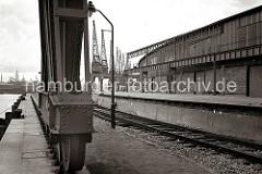 Die Laufräder des Halbportalkrans werden auf Schienen geführt, die auf der Kaimauer des Togokais verlaufen - das andere Ende des Portals wird an einem Eisengerüst an der Fassade des Schuppens 58 geführt.