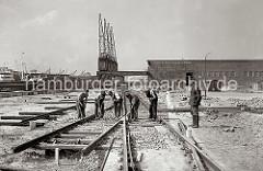 Die Gleisanlagen der Hamburger Hafenbahn werden beim Verteilungsschuppen 58 am Togokai des Südwesthafens verlegt. Bauarbeiter mit Spitzhacke bearbeiten den Schotter zwischen den Bahnschwellen.