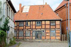 Historisches Fachwerkhaus in der Kirchenstraße Bützow; das jetzt leerstehende ehemalige Ratsarmenhaus steht als herausragendes Baudenkmal unter Denkmalschutz. Die Fenster sind  mit Holzplatten vernagelt, das Dach teilweise notdürftig repariert.