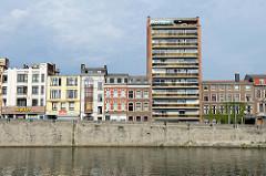 Blick über die Maas auf den Quai de la Dérivation in Lüttich / Liège; Wohnhäuser in unterschiedlichen Baustilen stehen am Flussufer.