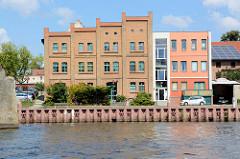 Blick über die   Hohensaaten-Friedrichsthaler Wasserstraße zum Kanalufer der Stadt Gartz / Oder; an der Uferpromenade steht ein historischer oder Speicher / restauriertes Backsteingebäude, daneben ein kubischer Neubau.
