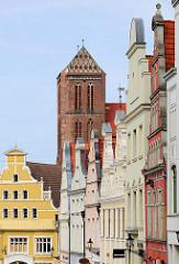 Historische Hausfassaden Hausgiebel in unterschiedlichen Farben in der Lübschen Straße von Wismar; Kirchturm der Sankt Nikolaikirche. Die Kirche wurde von 1381-1487  als Kirche der Seefahrer und Fischer erbaut. Sie gilt als Meisterwerk der Spätgotik