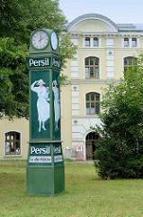 Alte Normaluhr mit der Reklame für das Waschmittel Persil; weiß gekleidete Frau mit Hut hält eine Packung in der Hand; Wiese am Lindgengarten in der Hansestadt Wismar. Im Hintergrund  das historisches Königlich Schwedisches Provianthaus, welches 1696
