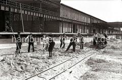 Der Hafenkai am Kaischuppen 58 wird gebaut; Bauarbeiter schaufeln Sand - drei Männer schieben auf provisorischen Gleisen eine mit Sand gefüllte Lore der Laderampe entlang.