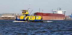Ein Schubschiff fährt Elbe abwärts, dahinter ein Massengutfrachter am Kirchenpauerkai im Hamburger Hafen.