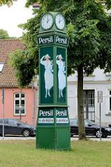 Alte Normaluhr mit der Reklame für das Waschmittel Persil; weiß gekleidete Frau mit Hut hält eine Packung in der Hand; Wiese am Lindgengarten in der Hansestadt Wismar.