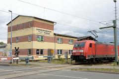 Gebäude mit Eisenbahnsymbol an der Fassade des Bahnbetriebswerks Wismar; schlichtes Verwaltungsgebäude.