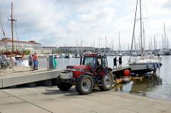 Mit einem Trecker wird an der Slipanlage der Marina an der weißen Wieck in Boltenhagen ein Segelschiff zu Wasser gelassen.