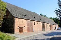 Lang gestrecktes Speichergebäude mit großen Holztoren in der Angermünder Straße von Oderberg; die Straße ist mit Kopfstein gepflastert.