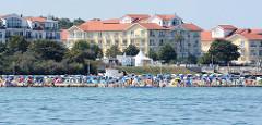 Blick auf den Ostseestrand mit Strandkörben und badenden Touristen in Kühlungsborn; dahinter Hotelgebäude.