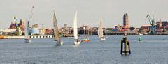 Blick über die Wismarer Bucht  zum HafenPanorama und den Kirchtürmen der Stadt Wismar; Segelboote segeln vor der Hafeneinfahrt.
