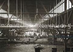 Lagerarbeiter im Bananenschuppen 48 am Amsinckkai des Segelschiffhafens prüfen die Qualität der Ware und legen sie auf ein Förderbahn. Die meisten der Hafenarbeiter tragen weisse Schürzen bei ihrer Arbeit.