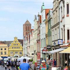 Innenstadt der Hansestadt Wismar, Einkaufstraße / Krämerstraße in der City; verschieden farbige historische Fassaden von denkmalgeschützten Wohn- und Geschäftshäusern - im Hintergrund der Kirchturm der Wismarer Sankt Nikolaikirche.