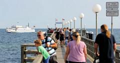Touristen auf der Seebrücke von Kühlungsborn,  die   1991 eingeweiht wurde; im Hintergrund das Ausflugsschiff / Fahrgastschiff Baltica.