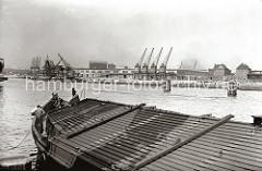 Im Vordergrund eine abgedeckte Schute am Afrikakai des Hamburger Südwesthafens - einige Schiffer befinden sich am Bug des großen Lastkahns. Auf der gegenüber liegenden Seite des Hafenbeckens die neu errichtete Kaimauer des Togokais.