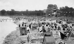 Historische Aufnahme vom Strandleben an der Ostsee in Boltenhagen, Strandkörbe stehen im  Sand,  andere in Strandburgen. Im Hintergrund eine Badetreppe, die ins Wasser führt.