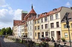 Wohnhäuser am Mühlenbach in Wismar, dahinter   das Kirchenschiff und Kirchturm der Sankt Nikolaikirche.
