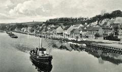 Schlepperverband mit mehreren Lastkähnen und einem Dampfschlepper mit hoher Schornstein auf der Alten Oder vor Oderberg. Kleine Boote liegen am Ufer, auf einer Wiese am Wasser wird Wäsche getrocknet.