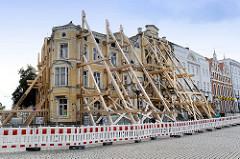 Denkmalgeschützte Wohnhäuser am Markt in Wismar, im April 2018 durch einen Brand teilweise zerstört - mit Holzkonstruktionen, schweren Balken gegen den Zusammenbruch abgestützt.