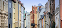 Farbige Fassaden an mehrstöckigen Wohnhäusern in unterschiedlichen Baustilen - Architektur in der Hansestadt Wismar.