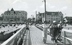 Historische Ansicht der  Seebrücke im Ostseebad Arendsee / Kühlungsborn; Hotels an der Strandpromenade - Liegestühle am Strand, Touristen in Badekleidung / Bademantel auf der Holzbrücke.