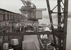 Blick von einem Halbportalkran auf den Güterumschlag im Hamburger Hafen - große Kisten werden über die an der Laderampe stehenden Güterwaggons verladen. An der Kaimauer vom Hafenbecken des Südwesthafens liegen mit Güter beladene Schuten.