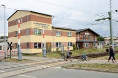 Gebäude mit Eisenbahnsymbol an der Fassade des Bahnbetriebswerks Wismar; schlichtes Verwaltungsgebäude sowie historischer Fachwerkschuppen - Fassade vom Ringlokschuppen.