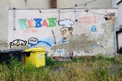 Hausfassade mit Werbung für einen Kebab Grill -  Malerei eines Kochs mit Messer, ablätternder Putz - Bilder aus Groß Strehlitz / Strzelce Opolskie.