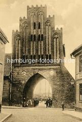 Historische Ansicht vom Wassertor in Wismar; das spätgotische Gebäude im Stil der Backsteingotik wurde 1450 errichtet, es ist Teil der ehemaligen Stadtbefestigung. Im Hintergrund sind Masten  von Schiffen im Wismarer Hafen zu erkennen.