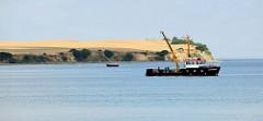 Ostseeküste bei Boltenhagen in Mecklenburg-Vorpommern - Steilküste bei Redewisch. An Bord vom Arbeitsschiff Sturmmöwe   wird mit dem Hydraulikkran gearbeitet, im Hintergrund ein Fischkutter.