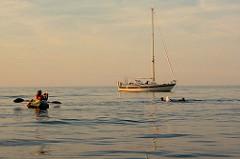 Abendstimmung auf der Ostsee bei Kühlungsborn; ein Segelboot liegt vor Anker - Menschen baden im Licht der untergehenden Sonne.