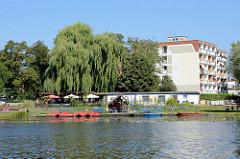Uferpromenade mit Wochenendhäusern und Tretbooten in Schwedt  (Oder); dahinter mehrstöckige Wohnblocks.