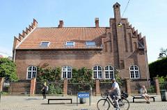 Klostergebäude mit neogotischem Treppengiebel; blühende Blumen / Rosen an der Hauswand, Ruhebänke in der Straße Algade / Roskilde.